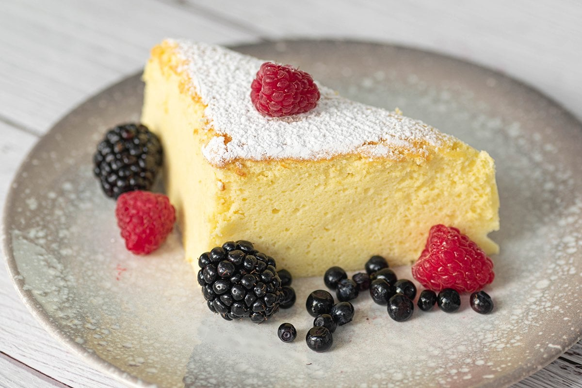 slice of japanese cheesecake on a gray plate with berries