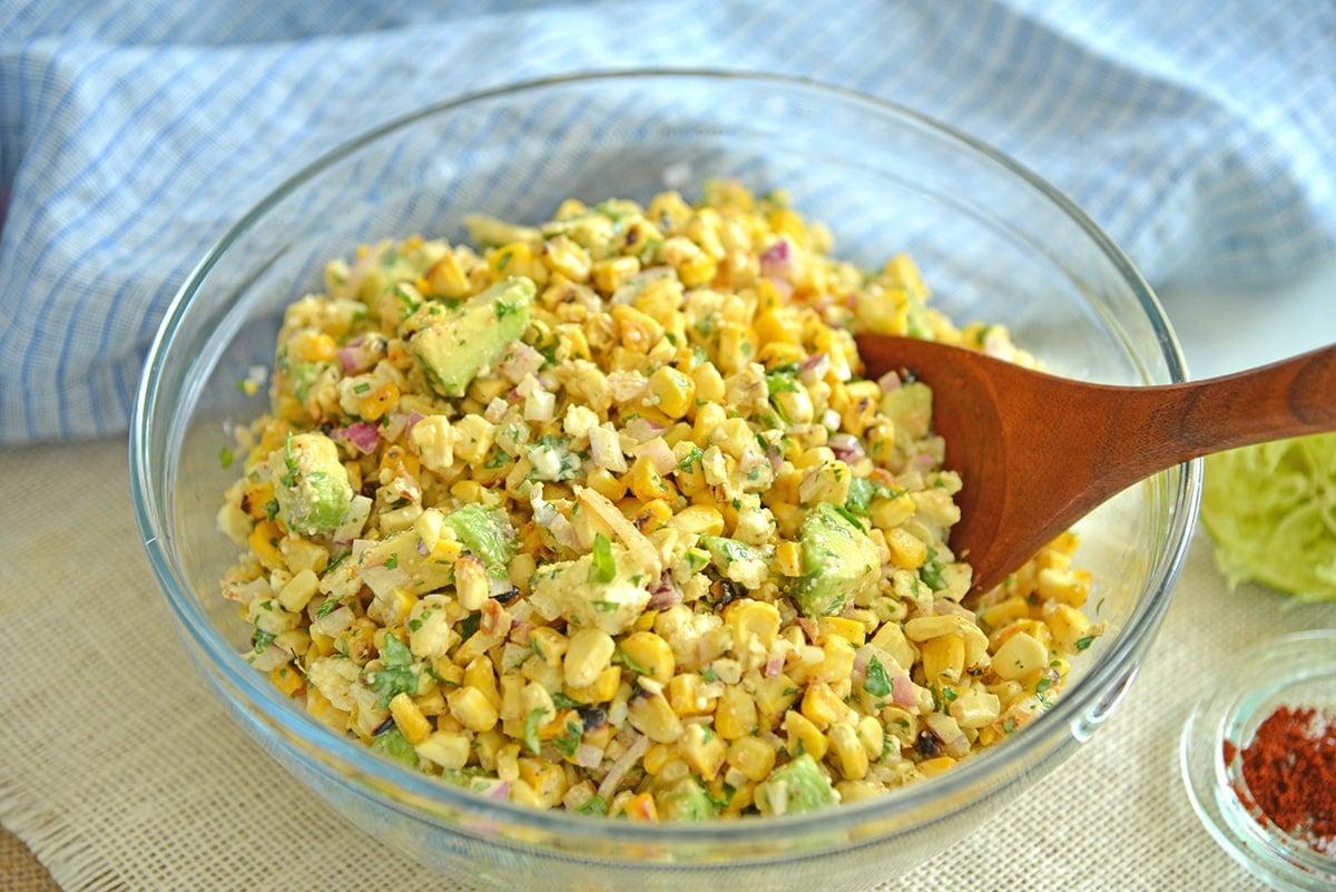 tossing corn salad ingredients