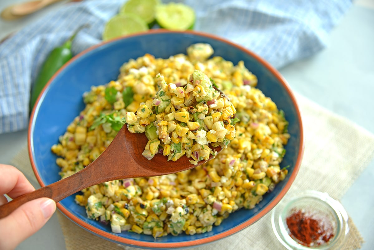 corn salad on a wooden spoon
