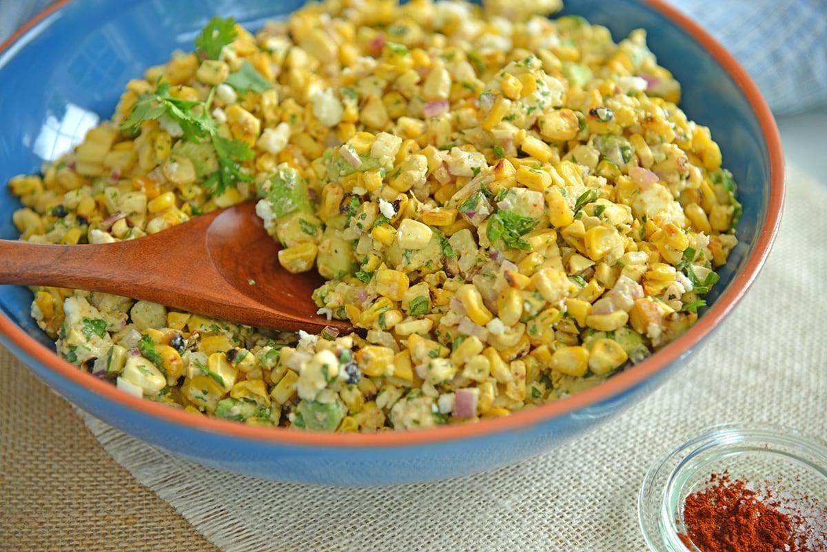 wooden spoon digging into a corn salad