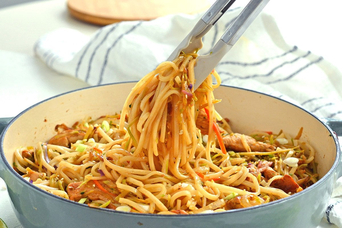 tongs picking up stir fry noodles in a pot