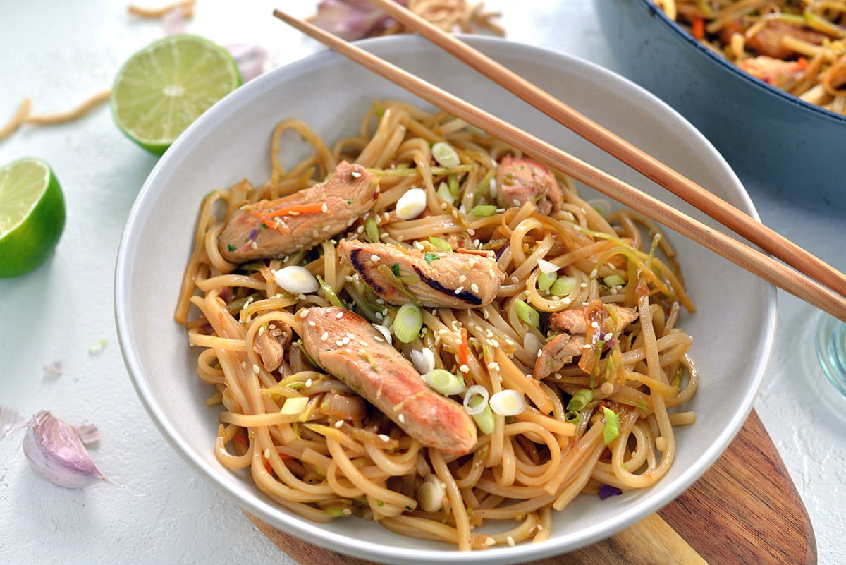 rice noodle stir fry in a white bowl with chopsticks