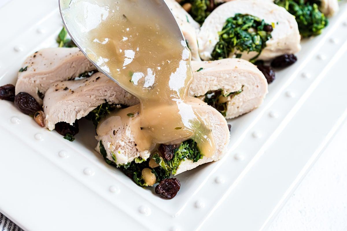 spooning gravy over spinach stuffed chicken
