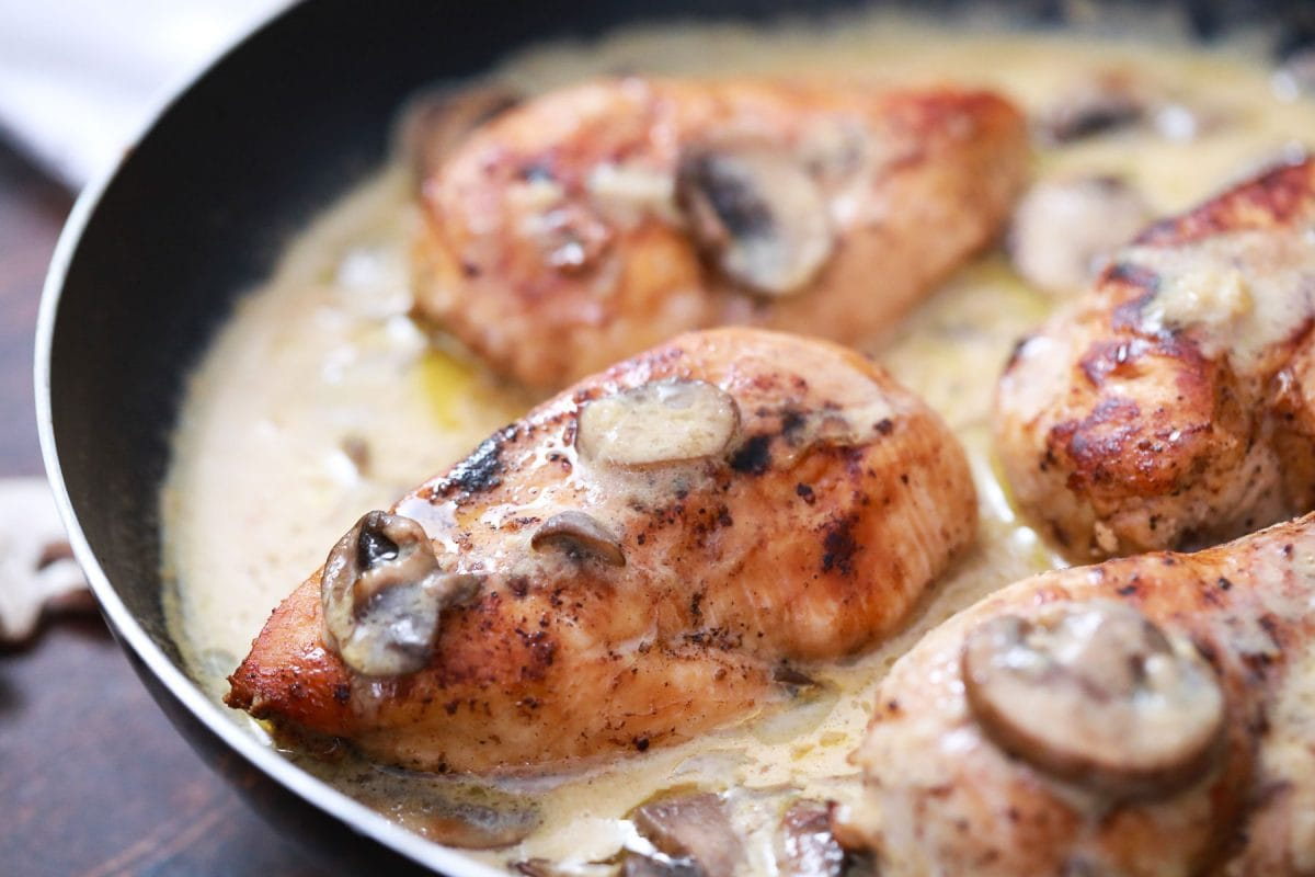 close up of a chicken breast in a cream sauce