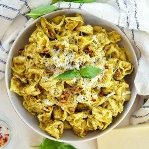 overhead of pesto tortellini in a cooking vessel