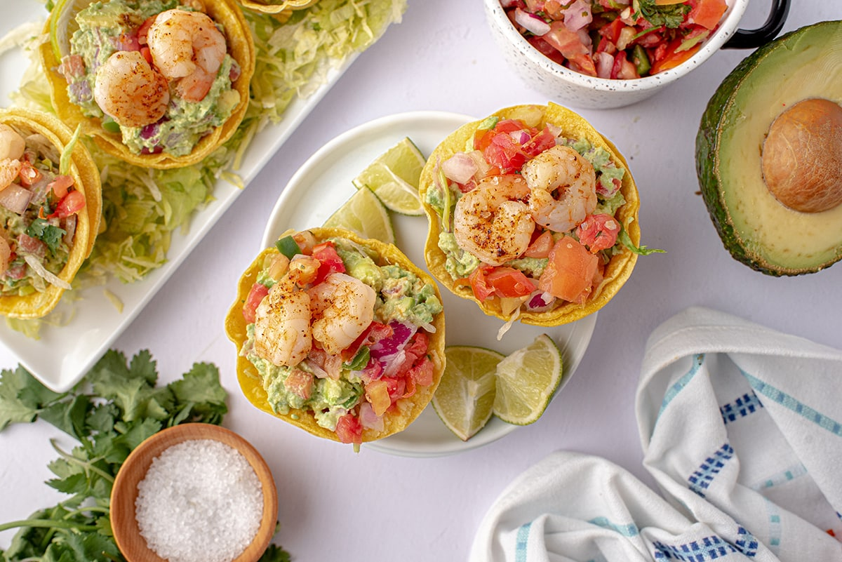overhead of tostada cups on a white plate with lime wedges