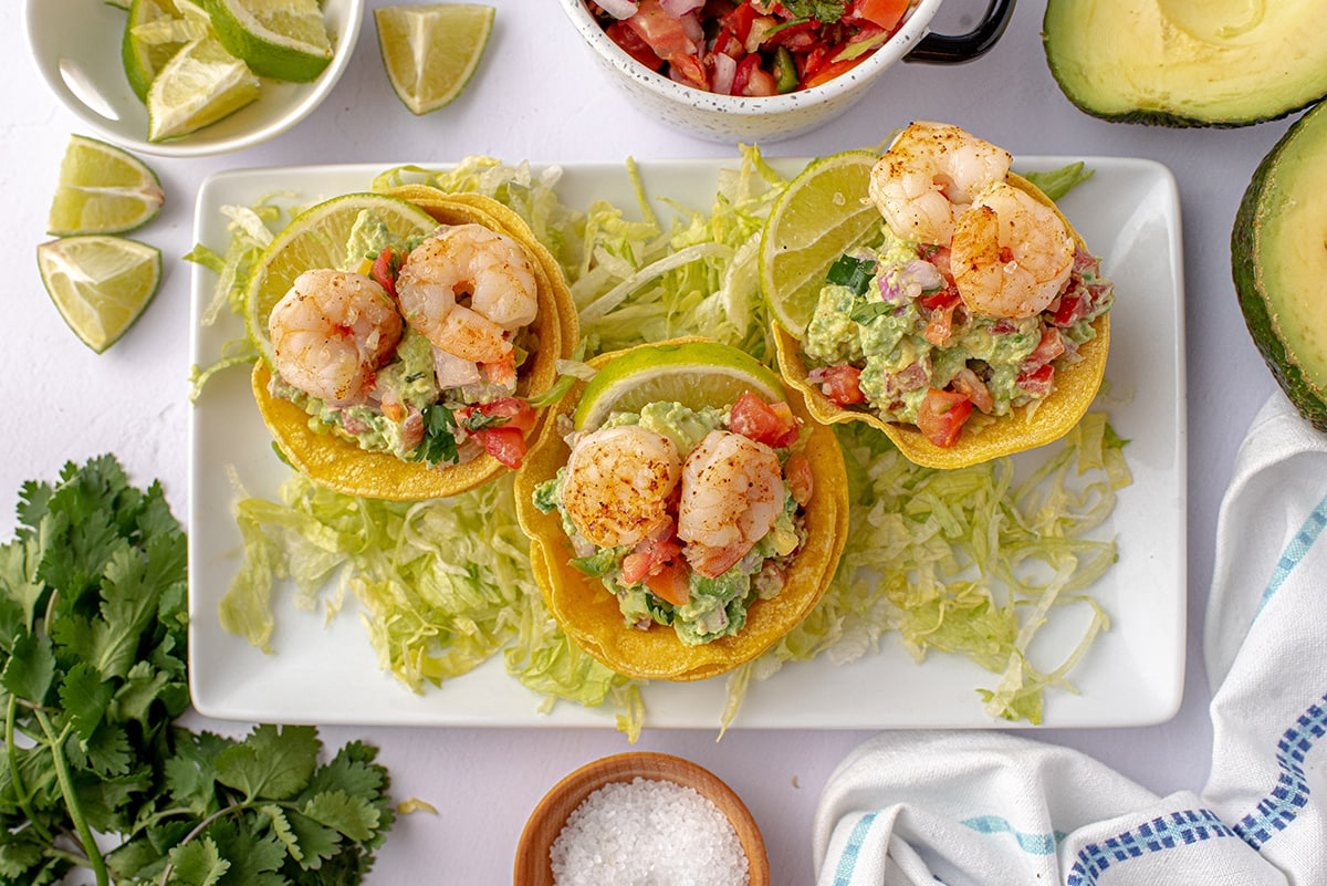 overhead of tostada cups on a serving platter with shredded lettuce