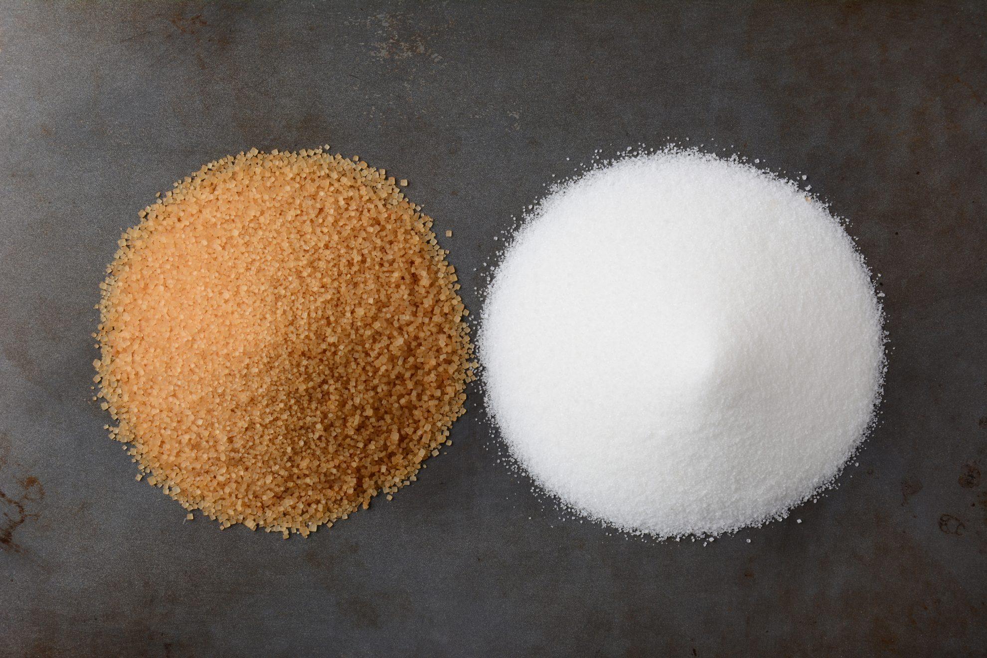 two piles of sugar- turbinado and white sugar