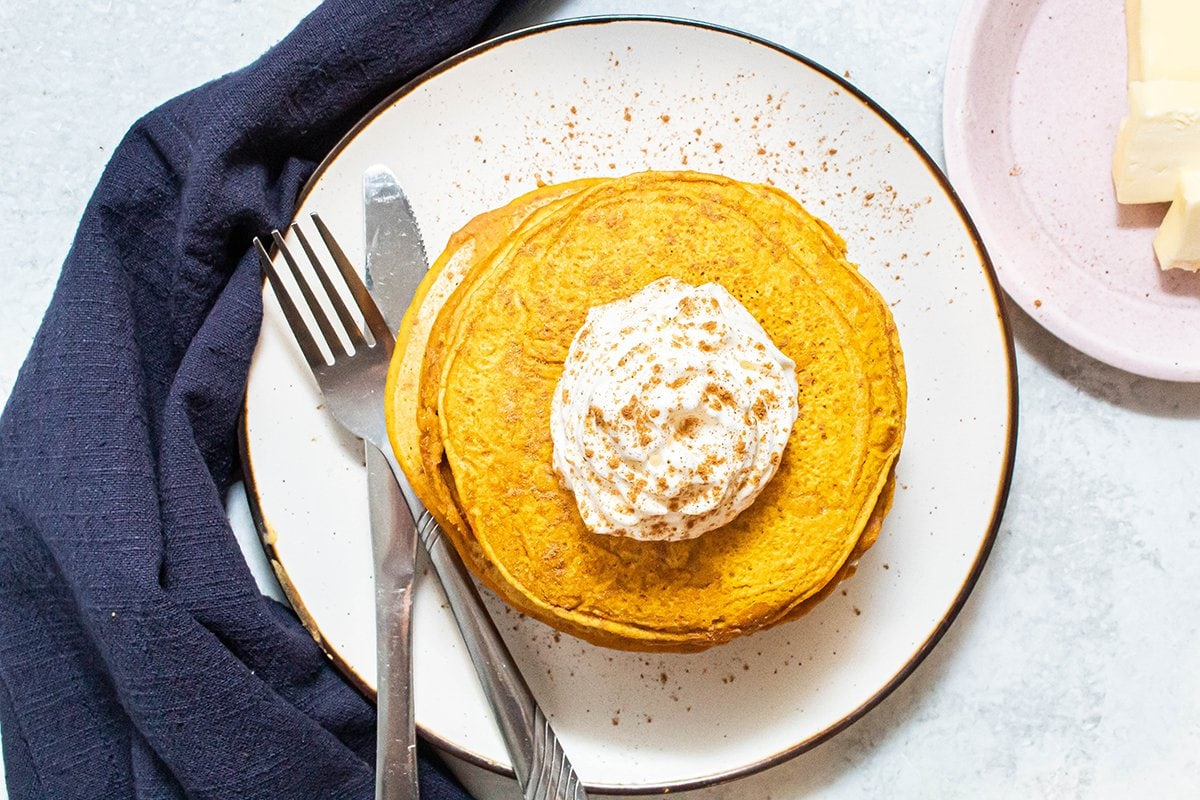 overhead of pumpkin pancakes with whipped cream